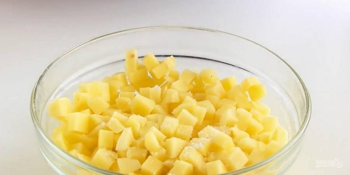 3. Картофель очистите и нарежьте очень мелкими кубиками. Смешайте с солью, перцем, приправами и измельченным чесноком. Форму диаметром 28 см смажьте растительным маслом.