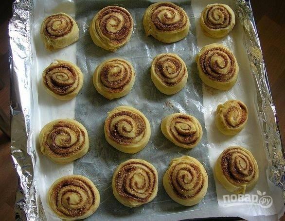 Скрутите тесто в рулет. Нарежьте его на кусочки в 3-4 см. толщиной. Выложите булочки на противень с пекарской бумагой, которую предварительно смажьте маслом.