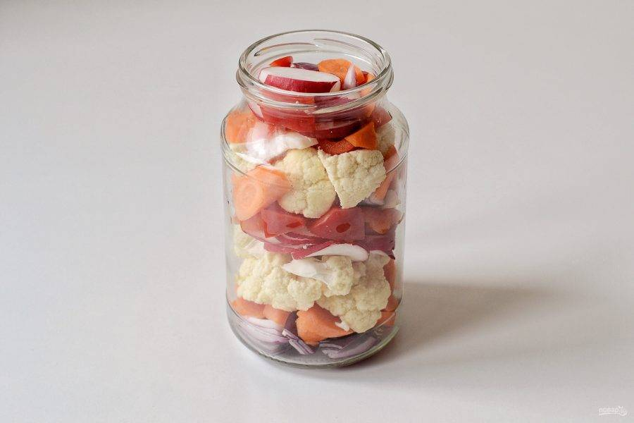 На дно заранее стерилизованной банки выложите лук, морковь, цветную капусту, болгарский перец, редис и чеснок слоями.