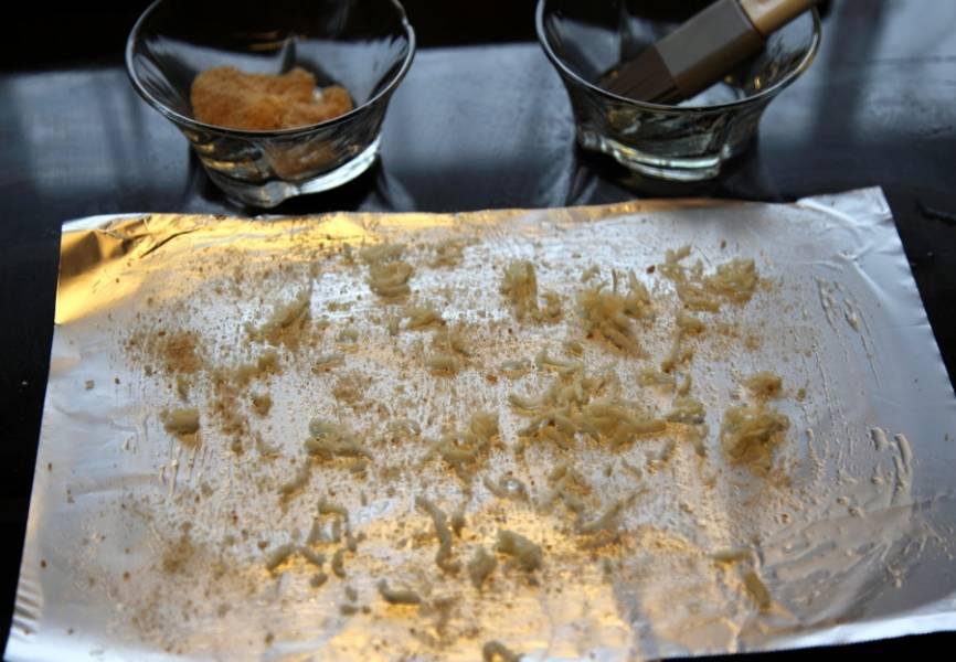 Берем лист фольги, смазываем маслом, посыпаем сухарями и сельдереем.