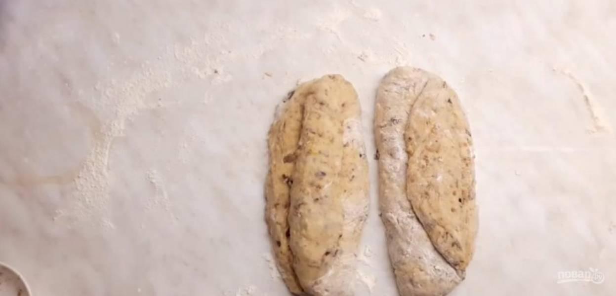 6. Затем высыпьте туда изюм, цукаты и измельченные в блендере орехи. Равномерно распределите орехи и сухофрукты в тесте. Немного вымесите тесто на столе, разделите его на две части и сформируйте штоллен. Растяните тесто и сверните его три раза так, как показано на фото.