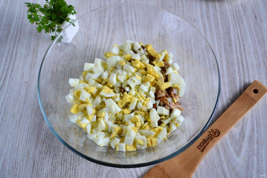 Яйца очистите и нарежьте кубиком, добавьте к грибам и курице.