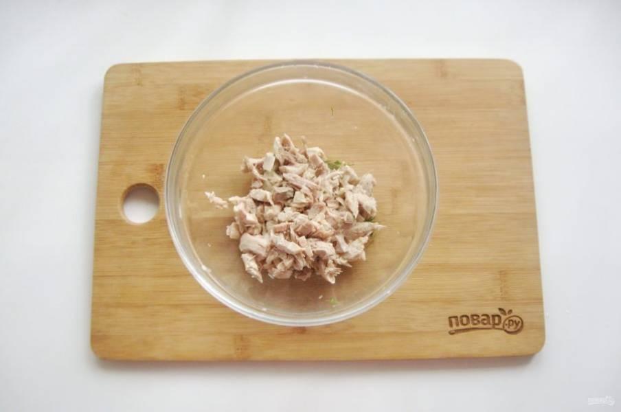 Тем временем приготовьте начинку в пирог. Отварную курицу мелко нарежьте и выложите в миску.