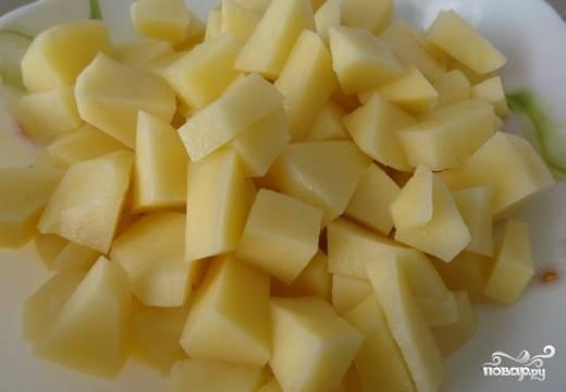 Тем временем почистим и нарежем небольшими кубиками картофель. Добавим его в кипящий бульон.