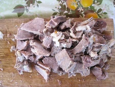 Затем шумовкой извлекаем из казана мясо, лук, морковь и чеснок, отделяем мясо от кости и нарезаем его на кусочки поперек волокон.