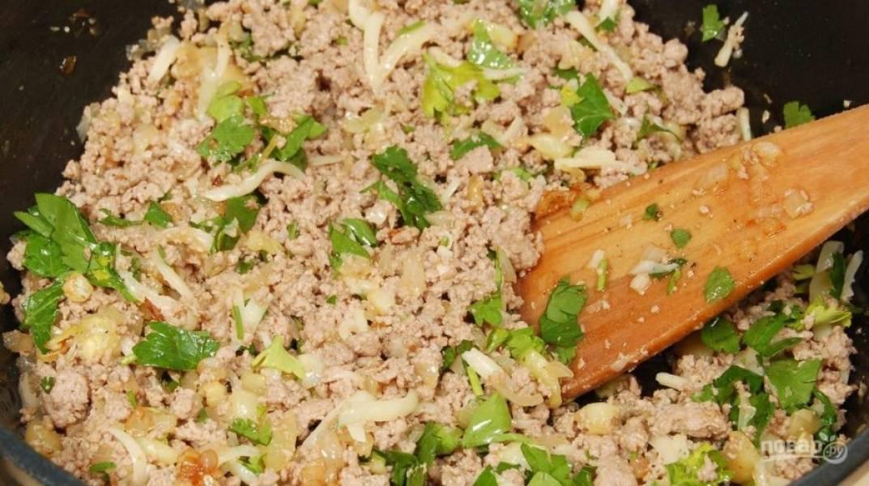 Приготовьте начинку. В масле на сковороде обжарьте мелко нарубленный лук и чеснок в течение 4-х минут. Затем к ним добавьте мякоть кабачков кусочками. Готовьте овощи 6 минут. Убрав овощи, в этой же сковороде, обжарьте фарш 10 минут. Добавьте к нему зелень, а потом смешайте с овощами.