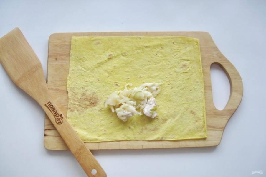 Смешайте капусту, сыр и курицу с луком. Лист лаваша нарежьте прямоугольниками и выложите начинку на каждый лист. Размер листа приблизительно 15х16 сантиметров.
