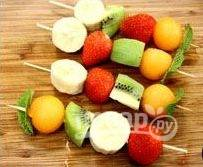 Теперь соберите «шашлыки из фруктов» на деревянные шпажки, чередуя кусочки различных фруктов и заканчивая каждый шампур листьями мяты.