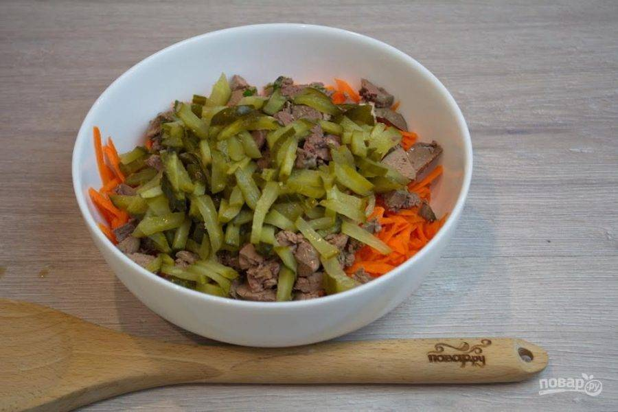 3. Соленые огурчики натрите на терке или мелко нарежьте ножом. Измельченные огурчики добавьте в салатник.