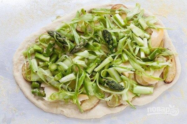 Разогрейте духовку до максимальной температуры. Спаржу вымойте и просушите. Порежьте, смешайте с маслом, солью и перцем, выложите на пиццу.