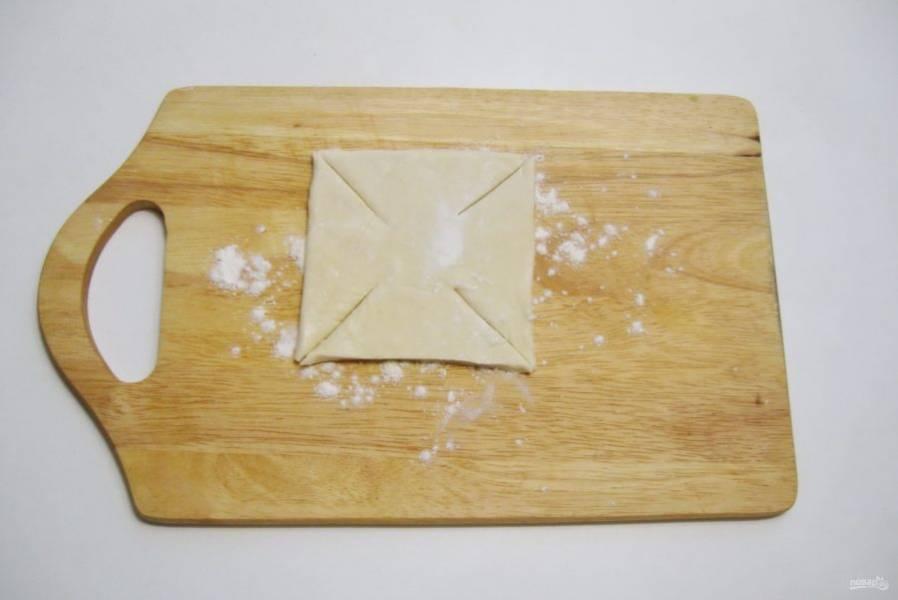 Слоеное тесто разрежьте на квадраты размером 10х10 см. Сделайте четыре надреза по углам.