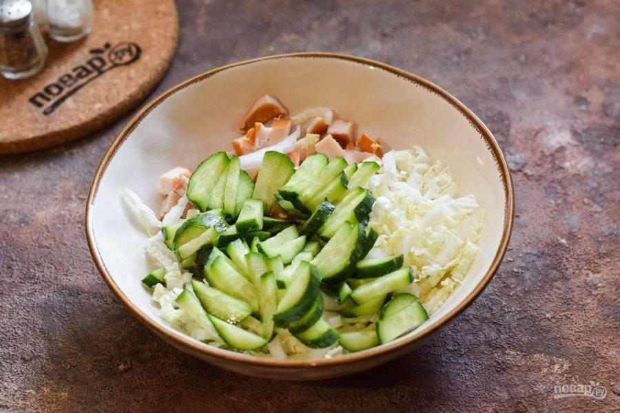 Переложите в салатник капусту и курицу. Свежие огурцы нарежьте небольшими полосками и добавьте в салат.