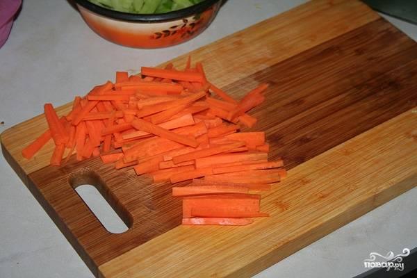 4. Нарезаем соломкой морковь, также отправляем ее на сковороду к мясу. Жарим до готовности, накрыв крышкой.