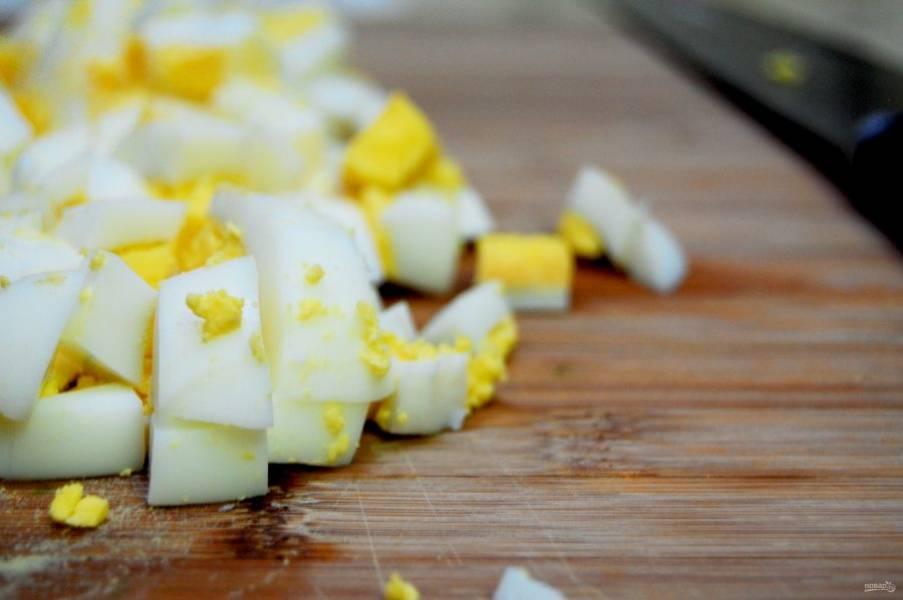 2. Также сварите вкрутую яйца и нарежьте. Горошек отварите 2 минуты в кипящей воде.