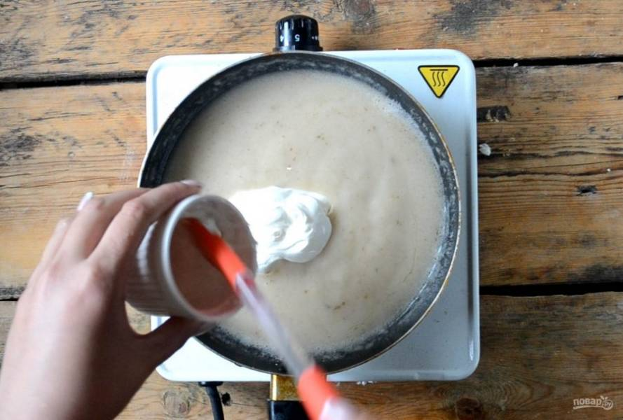 Последней отправьте в сковороду сметану, посолите и готовьте несколько минут.