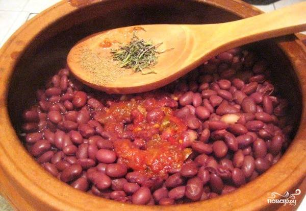 Выдавливаем чеснок и высыпаем в горшочек, поверх кладем аджику, нарезанный красный перец, добавляем соль и черный перец по вкусу.