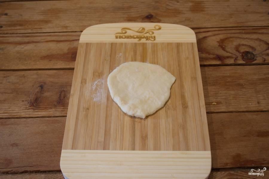 Отщипните комочек теста. Раскатайте его на доске. Припудрите мукой доску, чтобы тесто не липло.