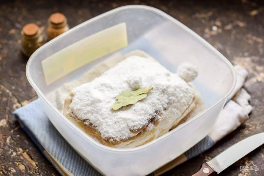 После засыпьте сало оставшейся солью, далее можете добавить чеснок, тмин, еще лавр. Натрите сало хорошо солью.