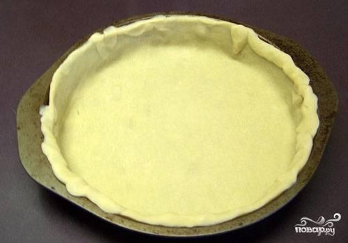 1. Первым делом включите духовку и разогрейте до 180 градусов. Форму для запекания смажьте немного маслом. Раскатайте довольно тонко тесто и выложите в форму. Также в этот рецепт идеально подойдет корж из крошки печенья со сливочным маслом.