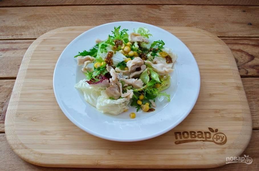 Консервированный кальмар достаньте из банки и нарежьте кусочками. Салат выложите на тарелку. Выложите кусочки кальмара хаотично.