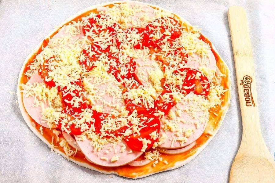 Твердый сыр измельчите на терке с мелкими ячейками и присыпьте всю заготовку пиццы сверху сырной массой. Поместите в духовку на 10-15 минут, следя за поверхностью выпечки.