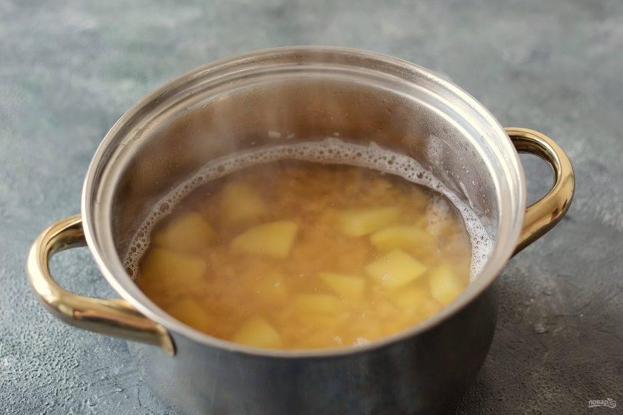 Налейте в кастрюлю воду, добавьте чечевицу и доведите до кипения. Добавьте картофель и варите суп 20 минут.