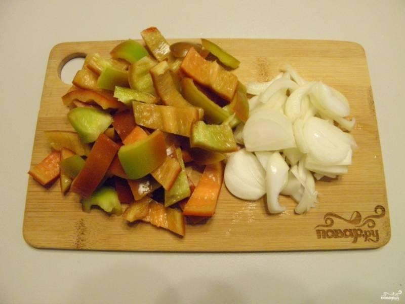 Очистите лук и порежьте полукольцами. Болгарский перец промойте и высушите, разрежьте, удалите хвостик и семена, порежьте кусочками.