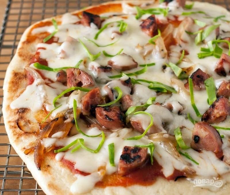 10.Переложите пиццу на разделочную доску, посыпьте рубленой зеленью.