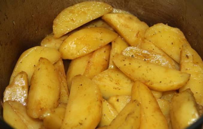 Со сваренного картофеля сливаем воду и заливаем соус. Накрываем кастрюлю крышкой и хорошенько трусим, чтобы соус равномерно распределился.