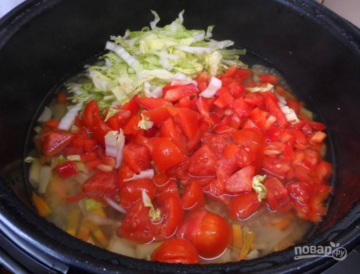 Добавьте капусту с томатами в чашу мультиварки. Готовьте ещё 3 минуты.