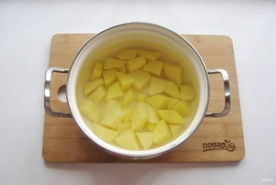 Картошку очистите, помойте, нарежьте и выложите в кастрюлю. Залейте водой и поставьте на плиту.