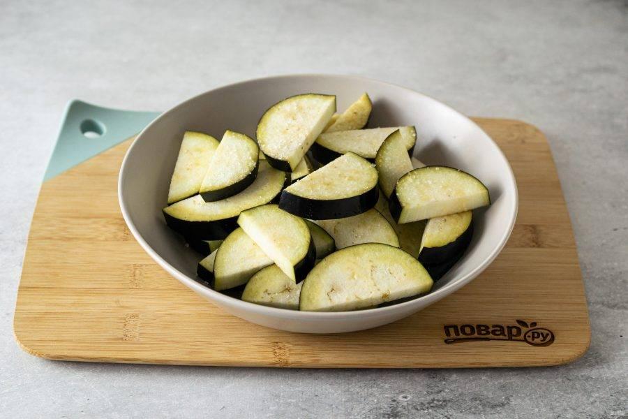Баклажаны помойте, разрежьте на крупные дольки и присыпьте 1/2 ч.л. соли. Перемешайте, оставьте на 15 минут.