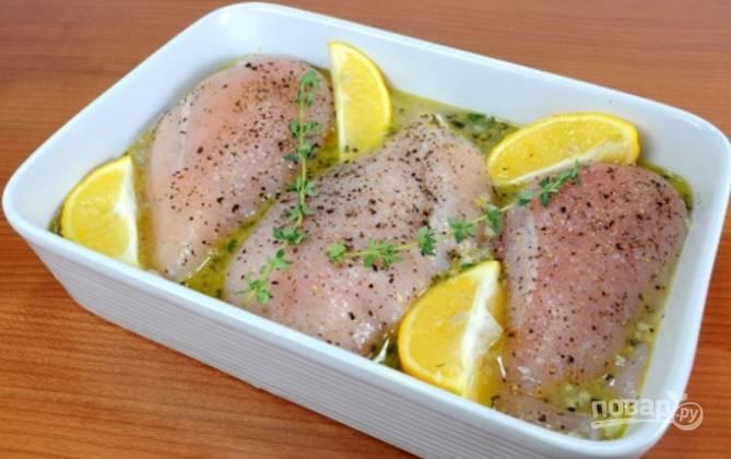 На сковороде разогрейте масло и буквально минутку обжарьте измельченный чеснок. Затем влейте туда куриный бульон, сок лимона, положите цедру, орегано и листочки тимьяна. Влейте эту жидкость в форму для выпечки и выложите туда курицу. Добавьте дольки лимона и веточки тимьяна. Посолите, поперчите.