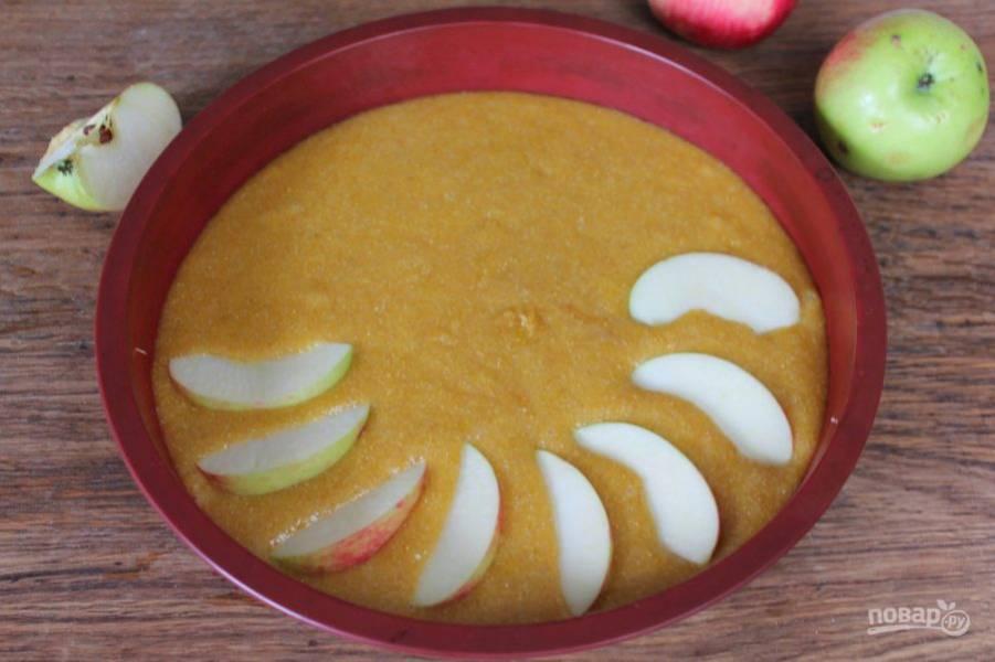 Тесто переливаем в силиконовую форму. Яблоки нарезаем дольками и выкладываем сверху.