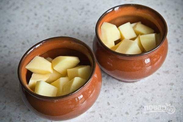 2. На дно горшочка отправьте чуточку масла и выложите нарезанный картофель, предварительно подсолив по вкусу.