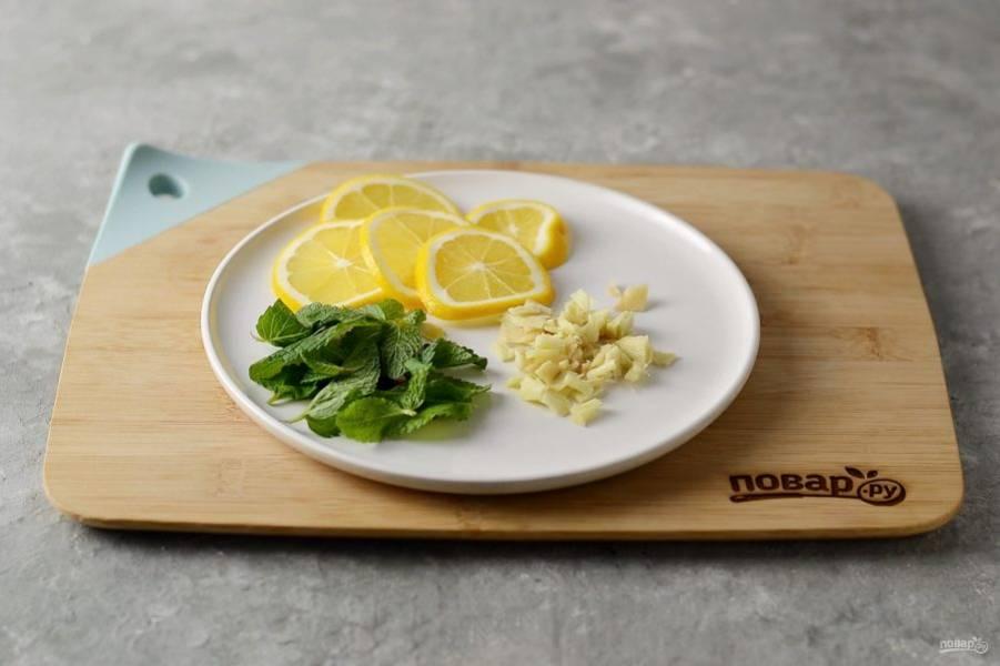 Лимон обдайте кипятком, затем нарежьте на тонкие кружочки. Имбирь очистите от кожуры, мелко порубите ножом. Мяту помойте, отделите листья от стеблей.