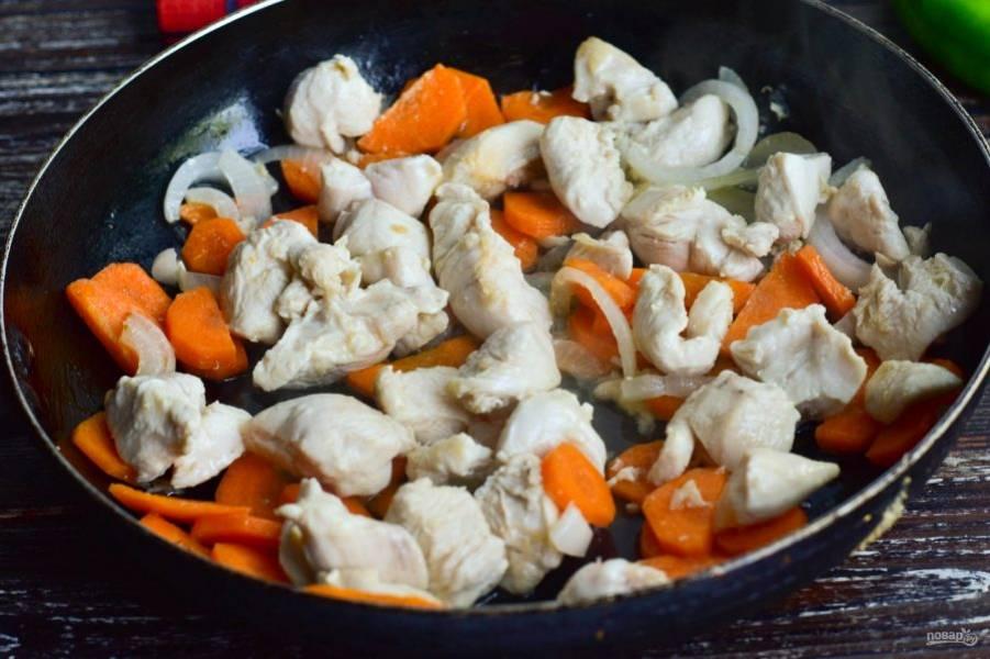 Нарежьте мясо, лук и морковь. В сковороде разогрейте растительное масло, выложите нарезанные продукты. Обжарьте их в течение 2-3 минут.