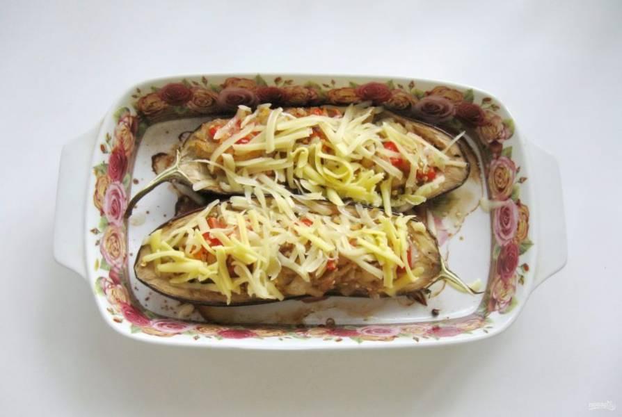 Выньте баклажаны из духовки и посыпьте тертым сыром.