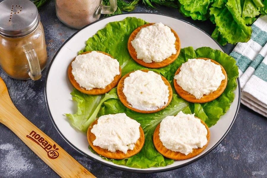 Выложите по 1 ч.л. сливочного сыра на крекеры. Если крекеры крупные, то выложите чуть больше сырной массы.