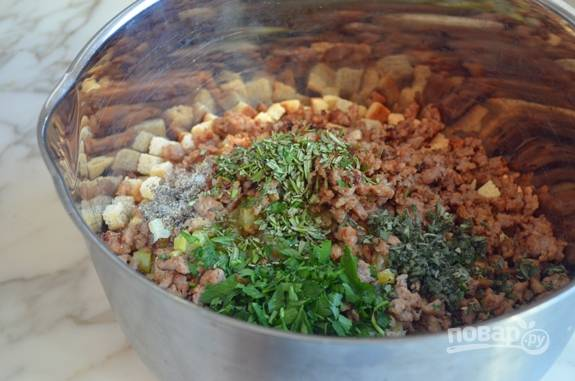 7. Следом туда же добавьте бульон, яйцо, мелко порубленную зелень, шалфей, розмарин, соль и перец.