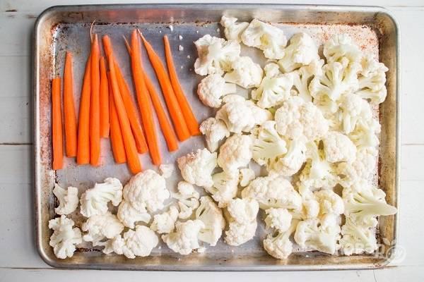 1. Вымойте и обсушите овощи. Разделите цветную капусту на соцветия и выложите на противень. Рядом разместите нарезанную тонкими ломтиками морковь. Сбрызните все оливковым маслом, посолите и поперчите, добавьте специи и отправьте в разогретую до 220 градусов духовку.