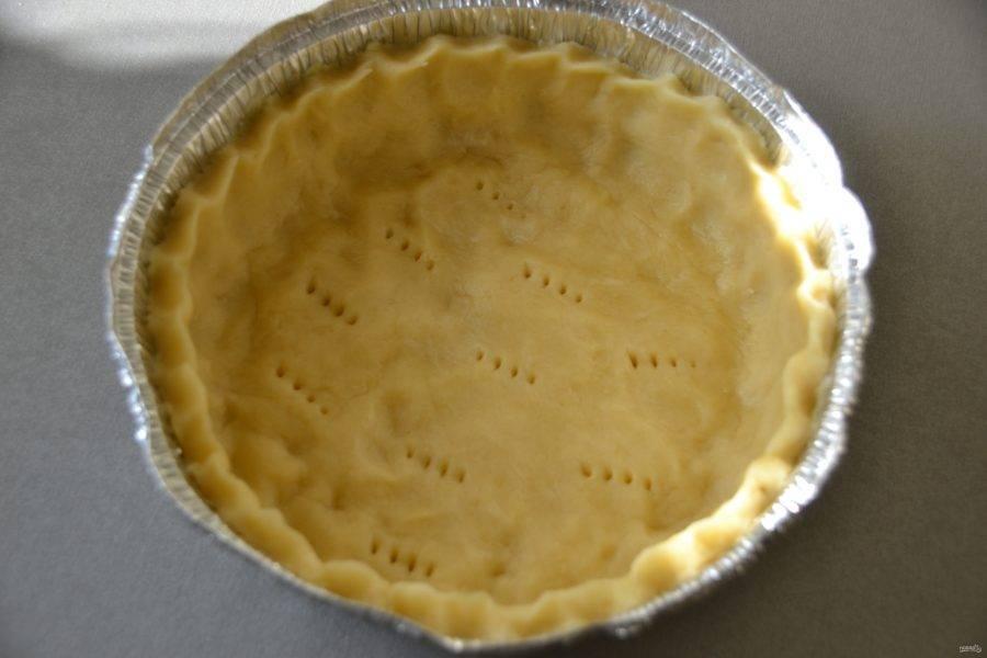 Выложите тесто в форму, (в данном рецепте использована форма диаметром 20 см.). Смазывать форму не нужно, так как тесто на основе масла. Сделайте высокие бортики, наколите дно вилкой.