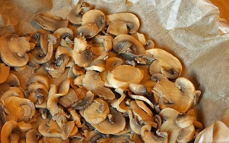 Форму для выпечки застилаем пергаментом, выкладываем слой грибов.