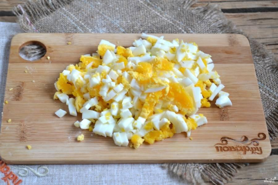 Заранее отваренные яйца порежьте мелкими кубиками.