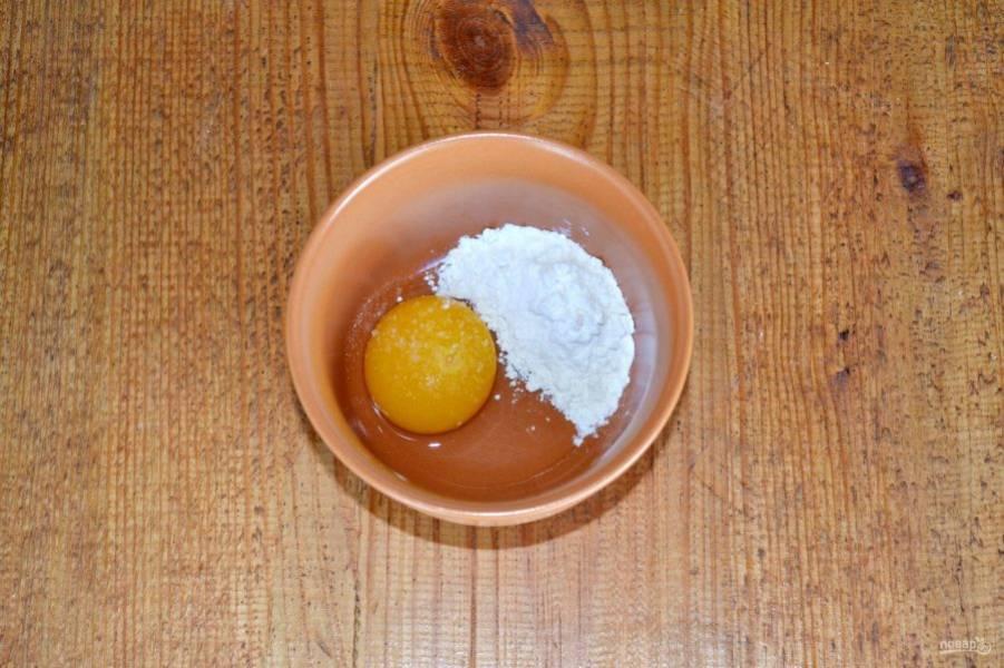 В небольшую мисочку вбейте яйцо, добавьте щепотку соли (не забывайте, что огурцы уже соленые) и муку.