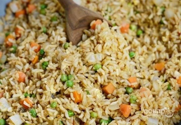 4. Затем в сковороду добавьте рис и соевый соус. Перемешайте.