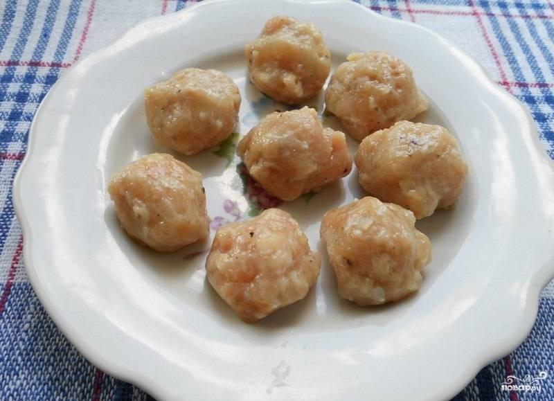 3.В миску перекладываем фарш, на терке измельчаем вторую луковицу, солим. Формируем небольшие шарики и складываем их на тарелку.
