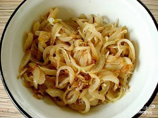 Достаем тесто из морозилки. Пока оно размораживается, займемся приготовлением начинки. Для этого лук чистим и режем полукольцами. Обжариваем его на сковороде до золотистости. Кладем соль и специи по вкусу.