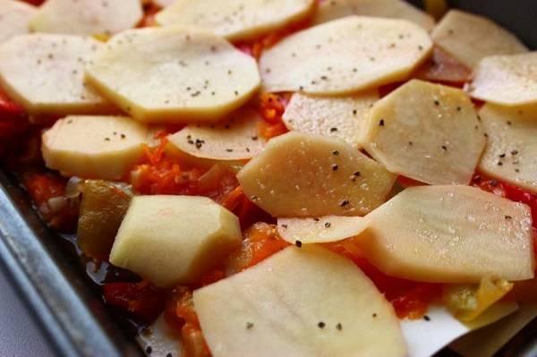 5. На дно жаропрочной формы выложить пару ложек томатного соуса. Застелить листами лазаньи и в произвольной последовательности выложить овощи. Кабачки, картофель и баклажаны предварительно подсолить и поперчить по вкусу.