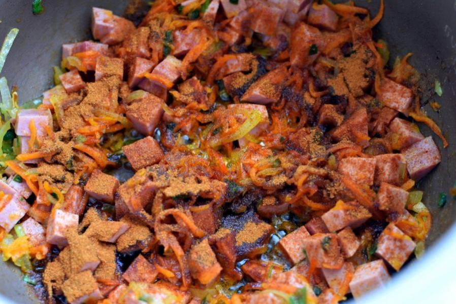 Выложите в чашу мультиварки нарезанную некрупными кубиками вареную колбасу и обжарьте до легкой корочки. Посыпьте паприкой и дайте ей окрасить масло в оранжевый цвет.